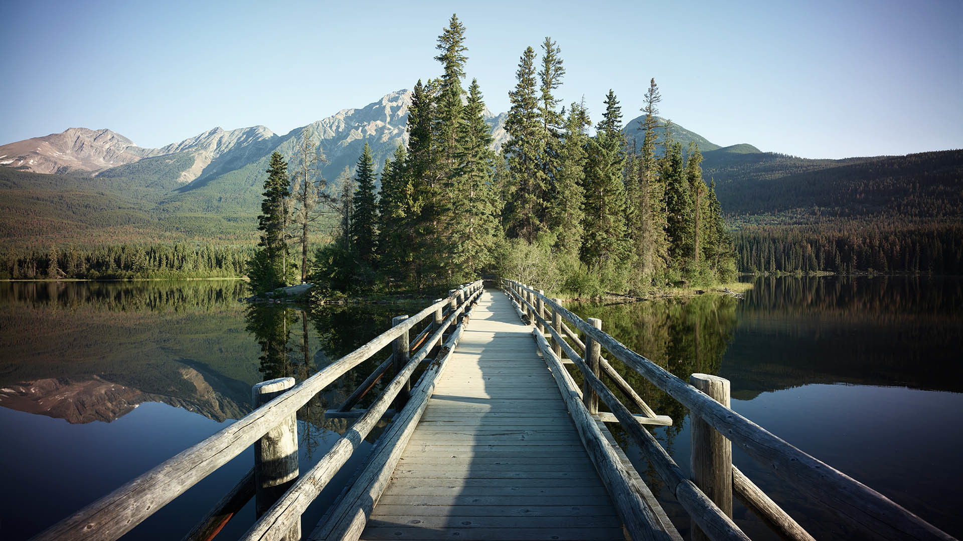Wooden bridge over mountain lake with fir forest on bank
